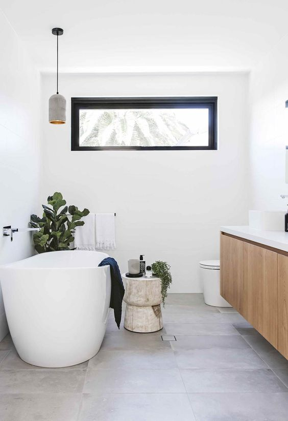 a contemporary bathroom with a floating vanity, an oval tub, a pendant lamp and a clerestory window plus some greenery