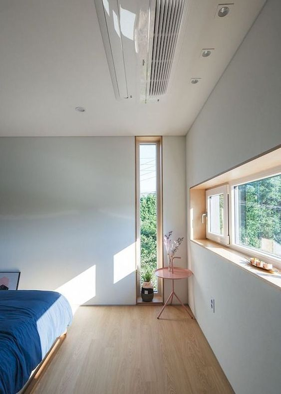 a contemporary bedroom with a long narrow window and a clerestory one, with blue bedding is chic