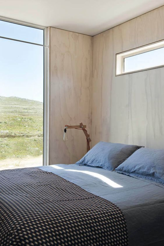 a contemporary bedroom with blonde wood walls, a comfy bed, a glazed wall and a clerestory window for additional light