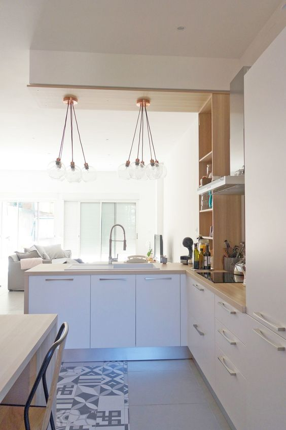 a contemporary white L shaped kitchen with butcherblock countertops and wooden shelves, with pendant lamps