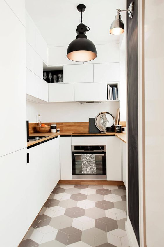 a contemporary white kitchen with sleek cabinetry, light stained countertops and a geometric tile floor