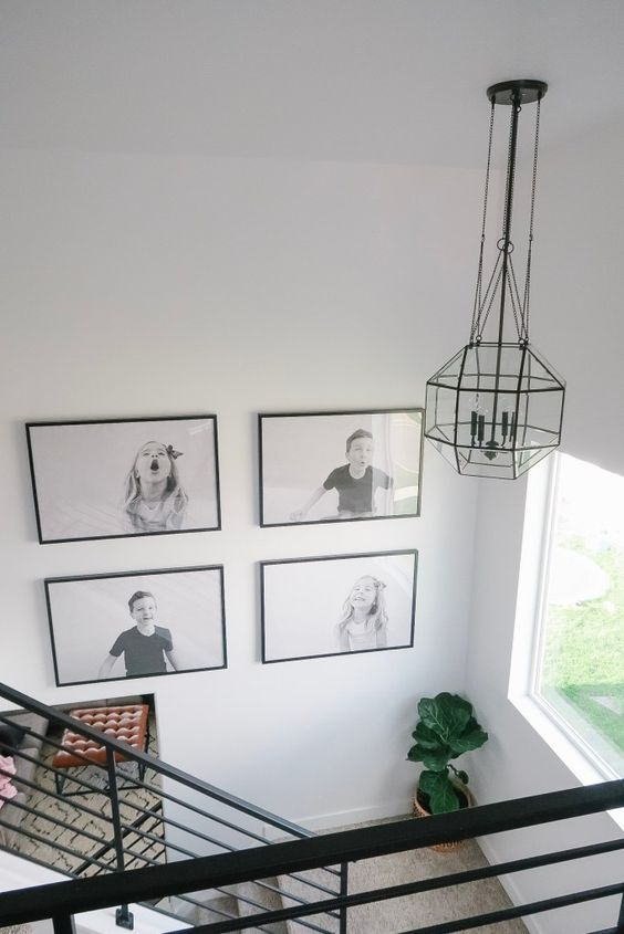 a cool black and white grid gallery wall with black frames shows off kids' pics and adds fun and coziness to the space