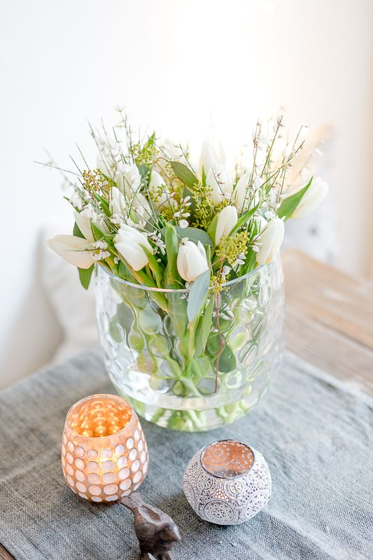 a cool clear vase with greenery and white blooms is a chic and simple spring arrangement or centerpiece to rock