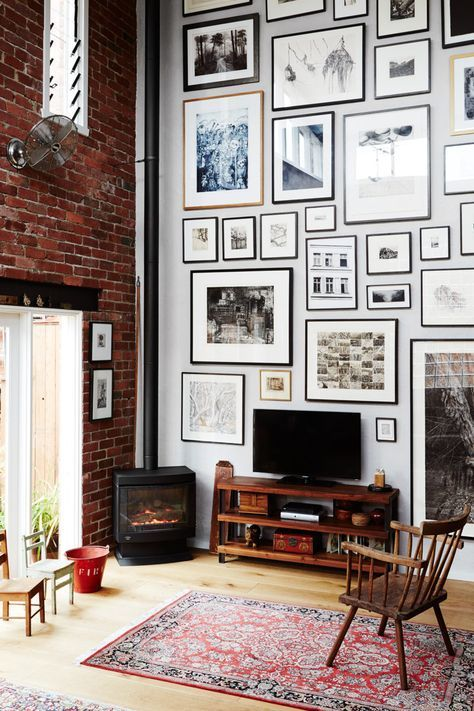 a cool gallery wall done with matching neutral and black frames of various sizes and with prints is a stylish idea
