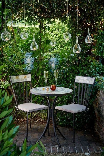 a cool garden eating space with hanging candleholders, a round table and chairs looks welcoming and cool
