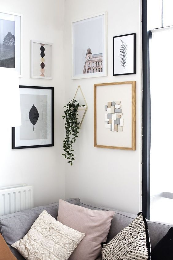 a cool modern gallery wall with mismatching white, black and neutral frames and various types of art plus hanging greenery