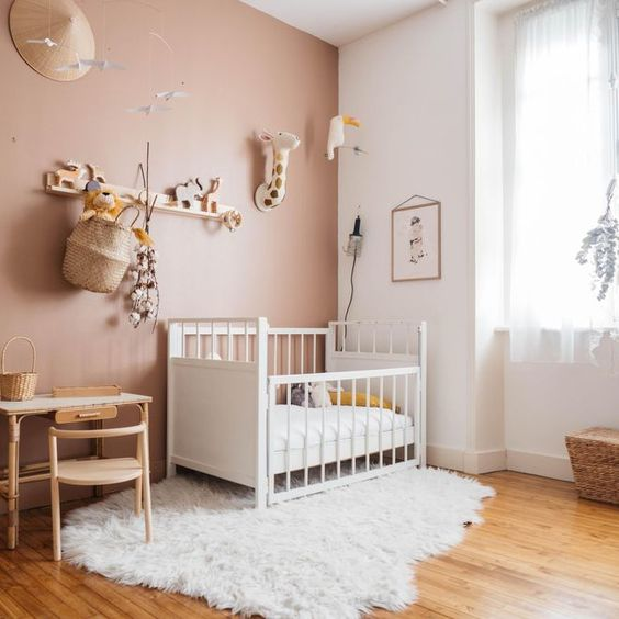 a cool nursery with a mauve accent wall, neutral and white furniture, a gallery wall and a shelf over the space