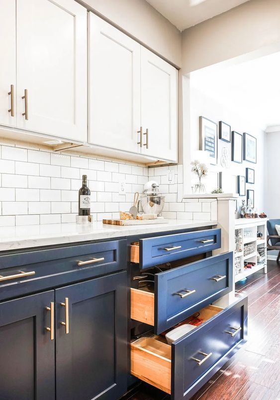 a cool two tone kitchen with navy and white shaker style cabinets, white quartz countertops and a white subway tile backsplash