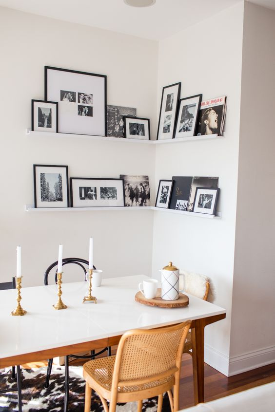 a corner gallery wall with black and white artworks in black frames adds personality to the space and makes it cozier