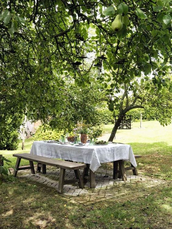 a cozy and simple dining space right in the garden, with simple wooden dining furniture – a table and benches