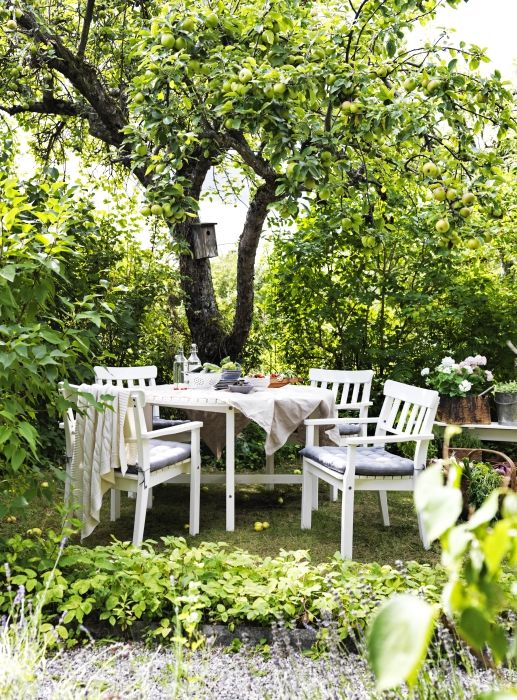 a cozy dining area done with IKEA furniture under the trees, with blooms and greenery around is cool