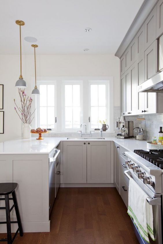 a cozy grey U-shaped kitchen with white stone countertops, a white marble tile backsplash and elegant lamps