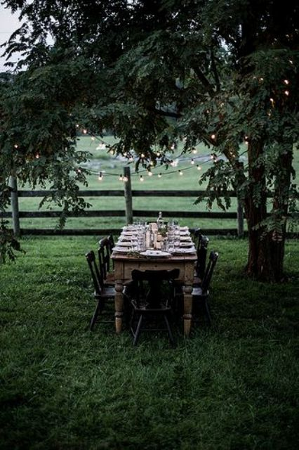 a cozy little dining area with a wooden table, black chairs and lights over it hanging from the tree