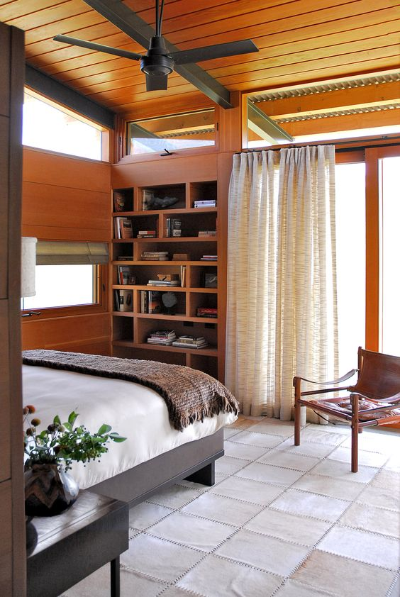 a cozy mid-century modern bedroom with a built-in shelving unit, a bed and a leather chair and some clerestory windows