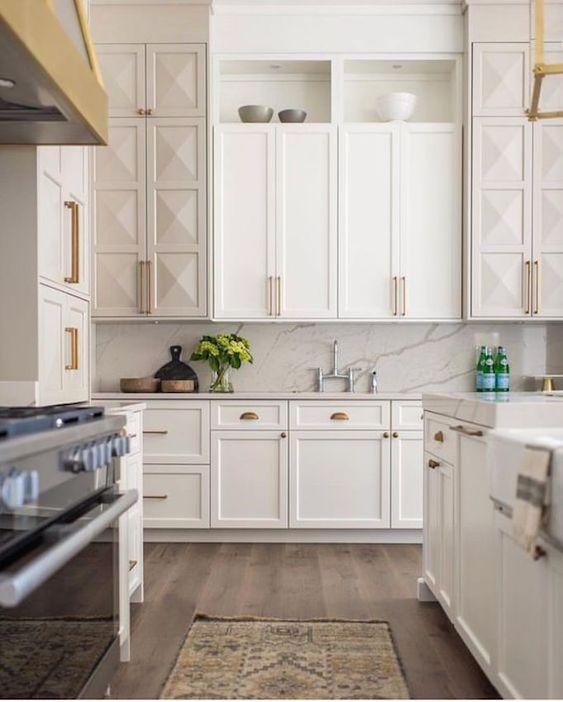 a creamy kitchen with shaker style and geometric cabinetry, a white marble backsplash and countertops plus gold and brass touches