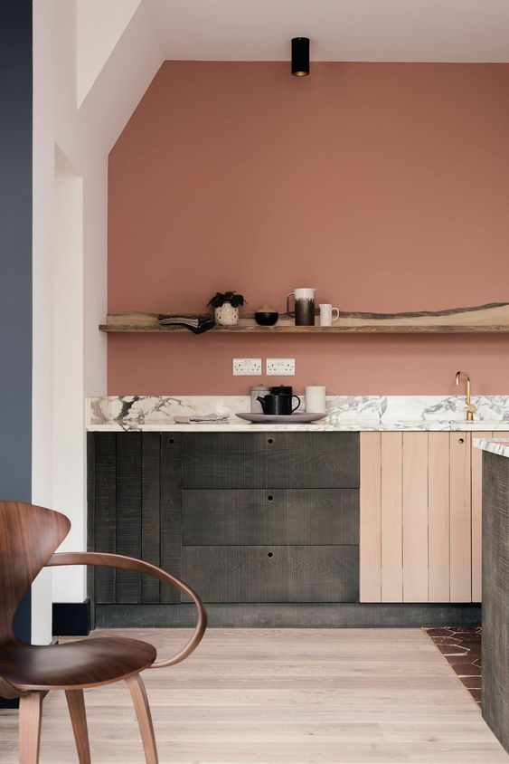a creatiive mauve kitchen with reclaimed wooden cabinets, a stone countertop and a rough wood shelf
