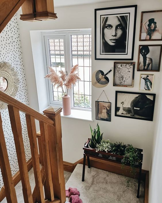 a creative free form gallery wall with mismatching frames, black and white artworks and a fan to style this space