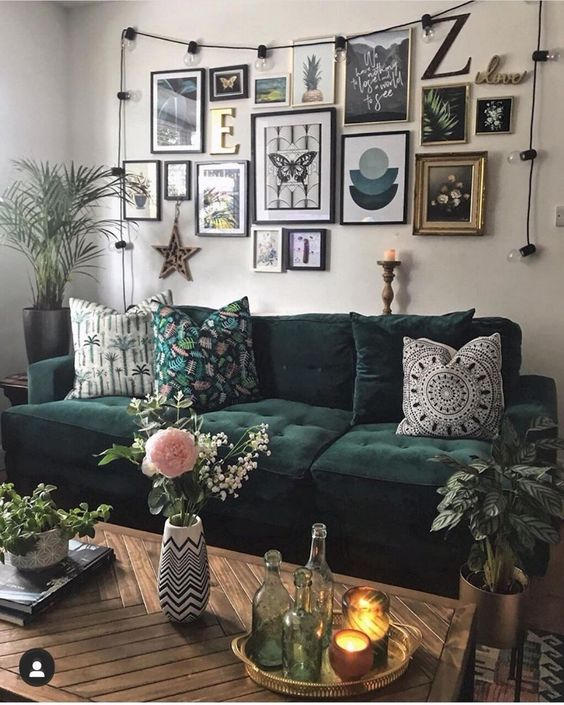 a creative gallery wall with black and gilded frames, black, white and green prints and artworks, lights, a monogram and a star of wood