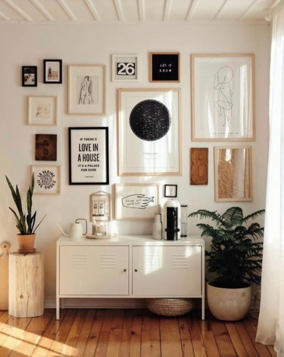 a creative gallery wall with black and white artworks in mismatching blonde wood frames and a couple black ones