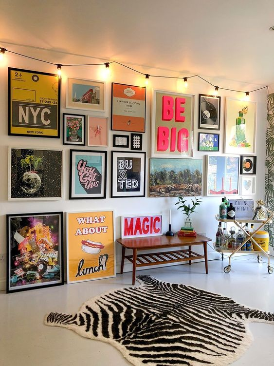 a creative gallery wall with bold and unusual artworks and posters in mismatching frames is a very bold idea