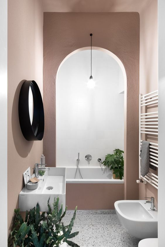 a creative mauve bathroom with an archway to the bathtub, a free-standing sink, a round mirror and plants