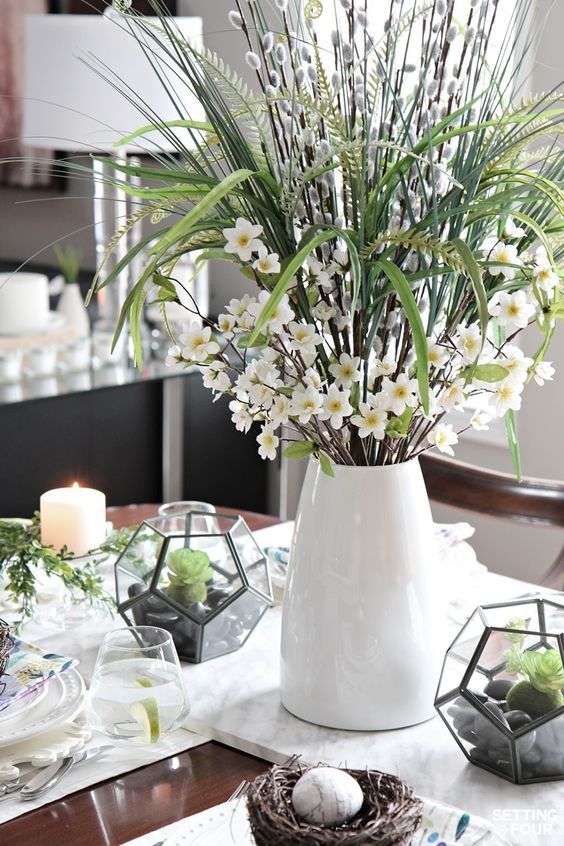 a creative spring centerpiece of a modern vase, willow, white blooms, greenery and grasses is a simple and cool idea