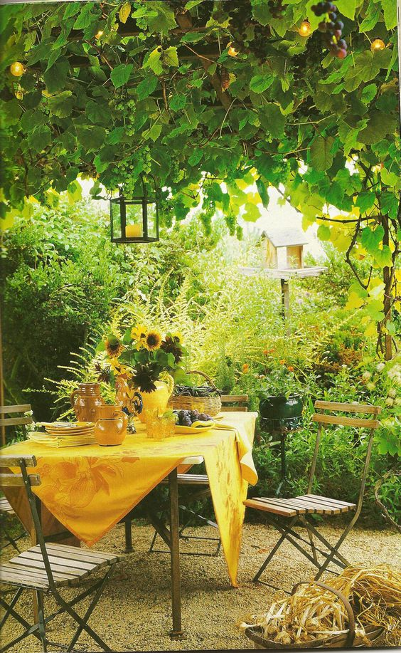a cute eating area with folding chairs and a metal table with lamps hanging from the trees and bright linens is wow