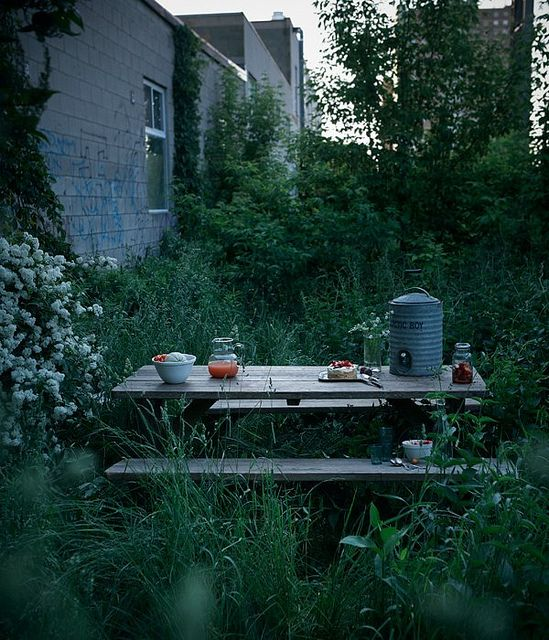 a cute rustic dining space with a table and benches placed right in the greenery and blooms