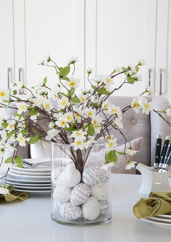 a cute spring to Easter centerpiece of a clear vase with graphic eggs and faux blooming branches is lovely