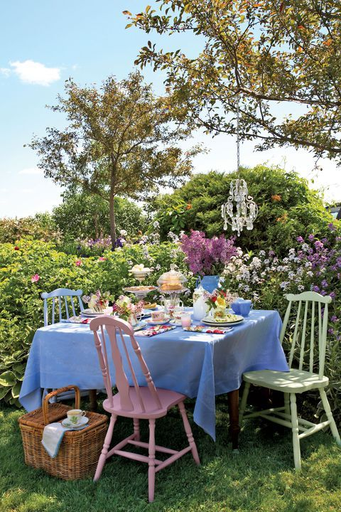 a cute vintage dining area right in the flowers, with a vintage table and matching pastel chairs plus a crystal pendant lamp