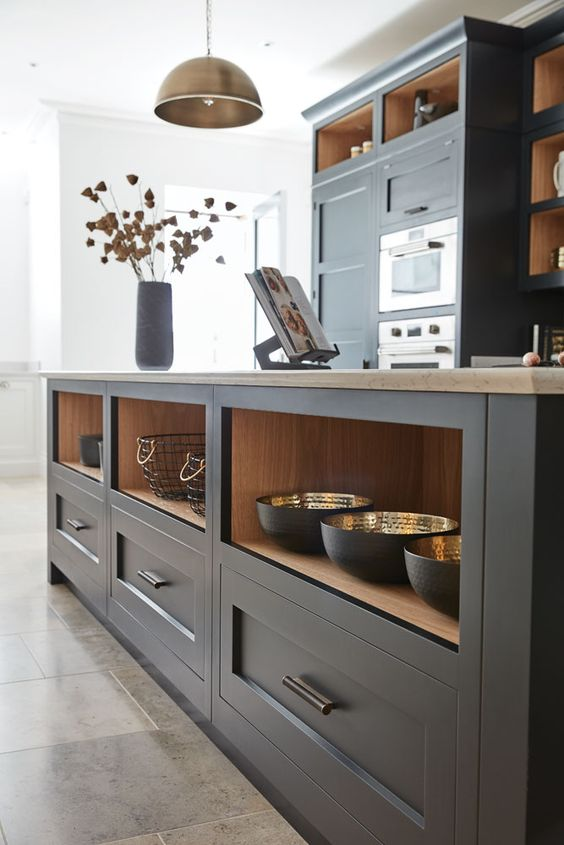 a dark grey shaker style kitchen with open compartments, butcherblock countertops, a metal pendant lamp and built-in appliances