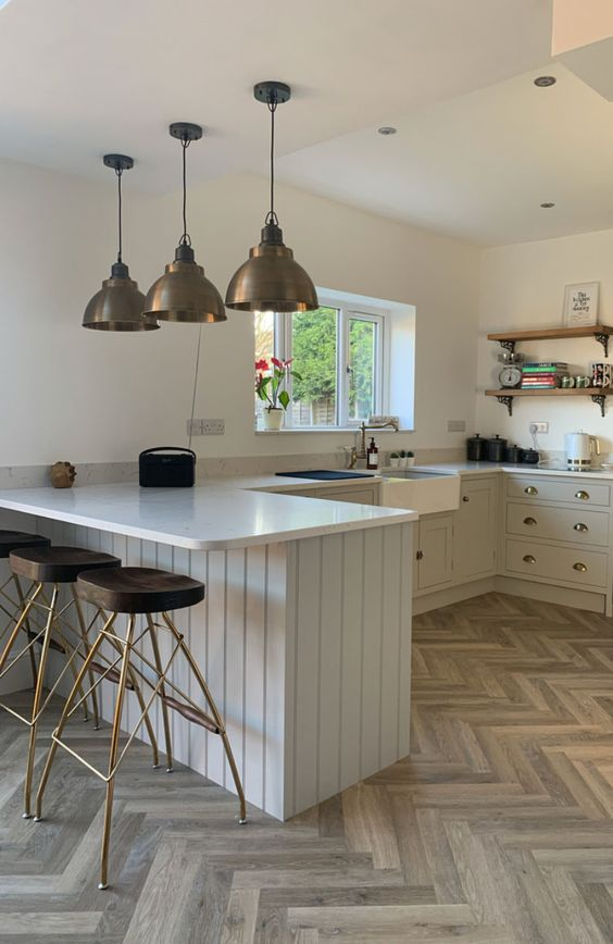 a dove grey U-shaped kitchen with white countertops, open shelves, metal pendant lamps and cool stools