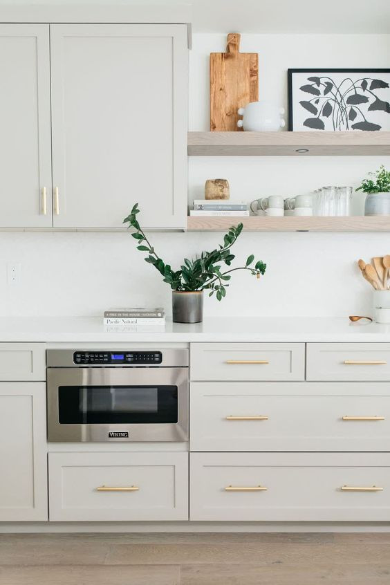 a dove grey kitchen with shaker cabinets, a white backsplash and countertops, floating shelves and gold handles is very elegant