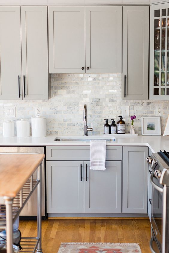 a dove grey shaker style kitchen with a white marble tile backsplash and white countertops plus black fixtures is chic