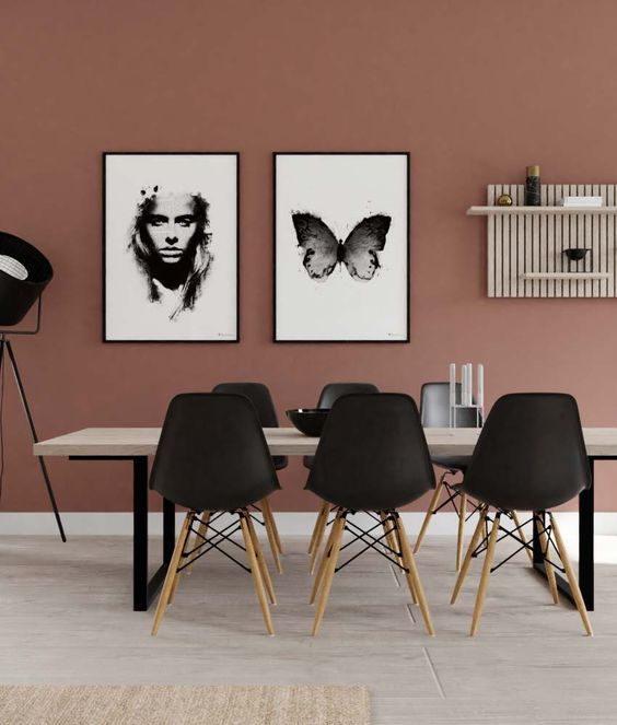 a fabulous mauve dining room with a mauve accent wall, a monochromatic gallery wall and cool chairs and a table