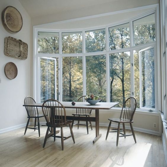 a farmhouse dining zone by a large bow window, with a vintage table and chairs plus decorative baskets on the wall