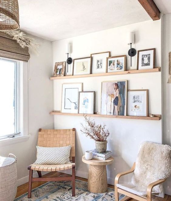 a farmhouse gallery wall with stained wooden ledges, colorful artworks and family makes the space more welcoming and cozy