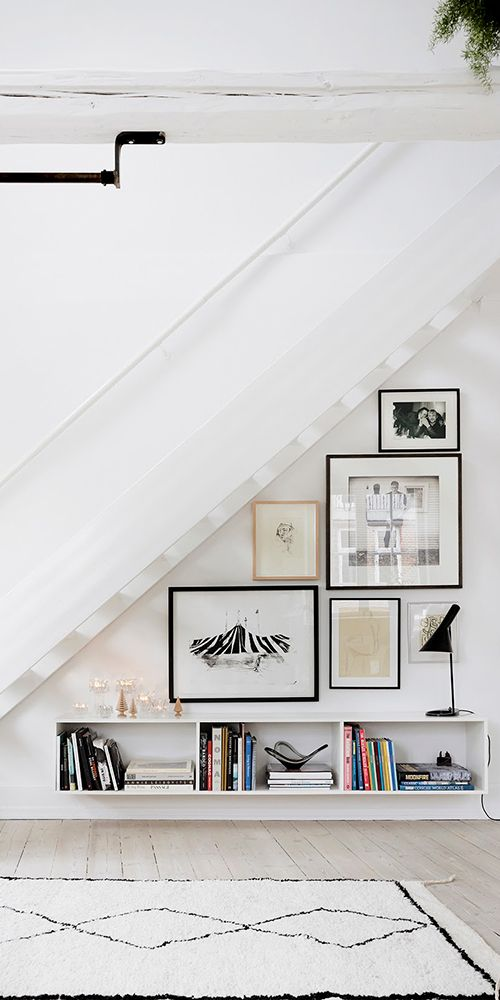 a free form gallery wall on the staircase, with mismatching frames and black and white artworks and photos