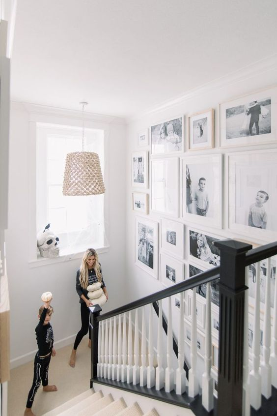 a free form gallery wall with black and white family pics and white frames si a very chic and stylish idea for any space