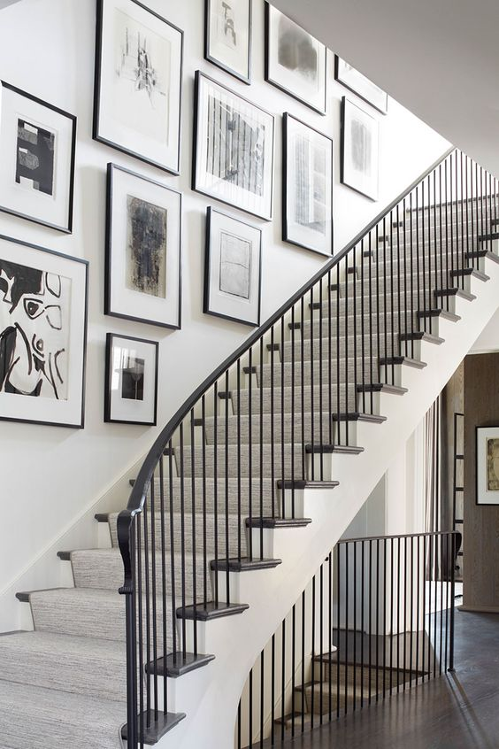 a free form gallery wall with black frames and black and white artworks adds elegance and chic to the space and makes it artful