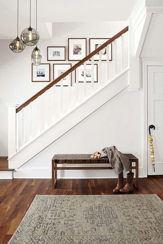 a free form gallery wall with colored family photos is a fresh and cool idea to spruce up the space over the stairs