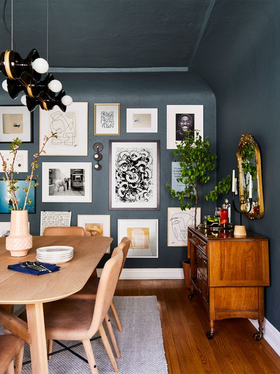 a free form gallery wall with framed and non-framed artworks, posters and prints plus some wall sconces is pure chic