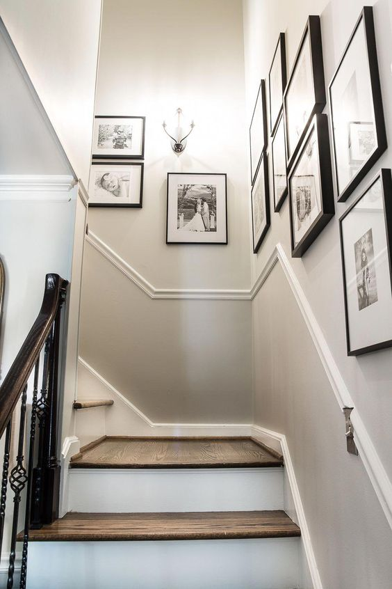 a free form gallery wall with matching black frames and black and white family pics is a lovely and artsy way to display the photos