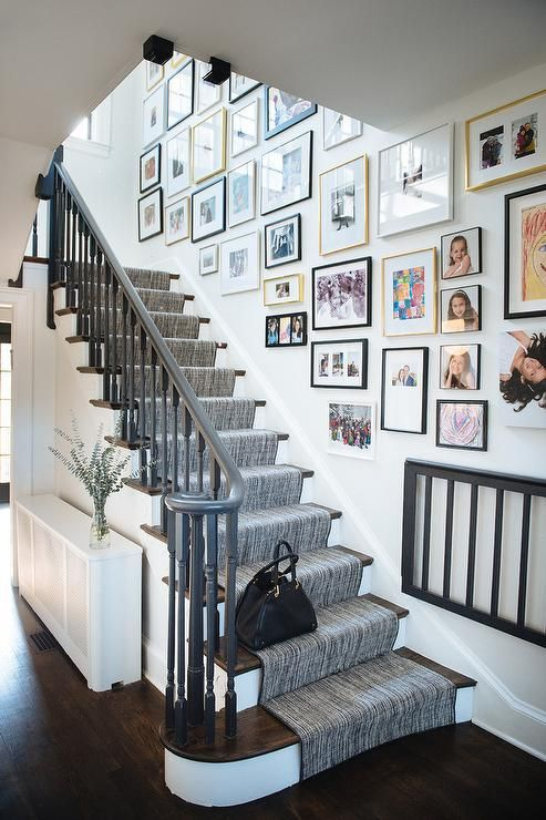 a free form gallery wall with mismatching frames and bold and black and white artworks and family pics is a cool idea