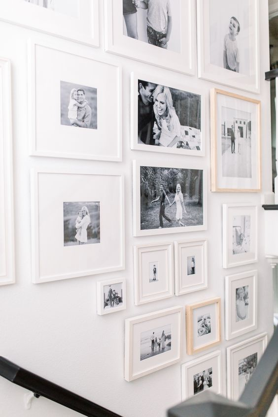 a free form gallery wall with mismatching frames, black and white photos is a stylish and chic idea with an eclectic feel
