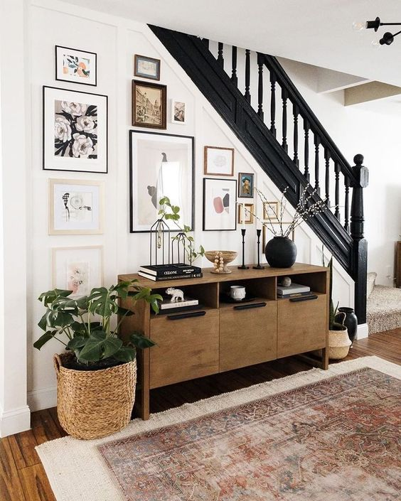 a free form gallery wall with mismatching frames right on the stairs, and various botanica artworks is wow