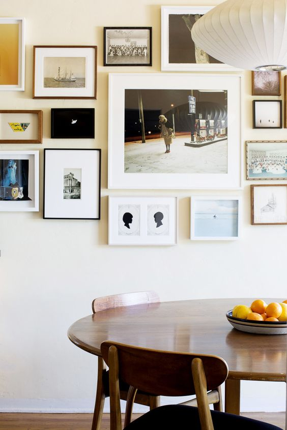 a free form gallery wall with thin black, white and wooden frames and white matting but mismatching black and white and color art