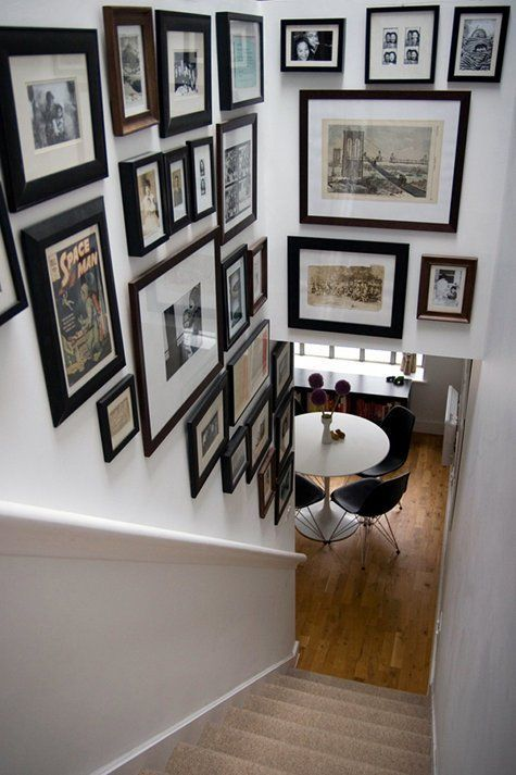 a free form gallery wlal over the staircase with mismatching frames and various types of retro and vintage art