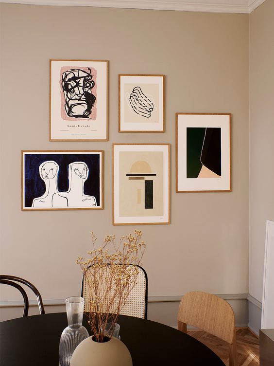 a free form modern gallery wall with thin gilded frames and graphic artworks for a chic modern touch in the space