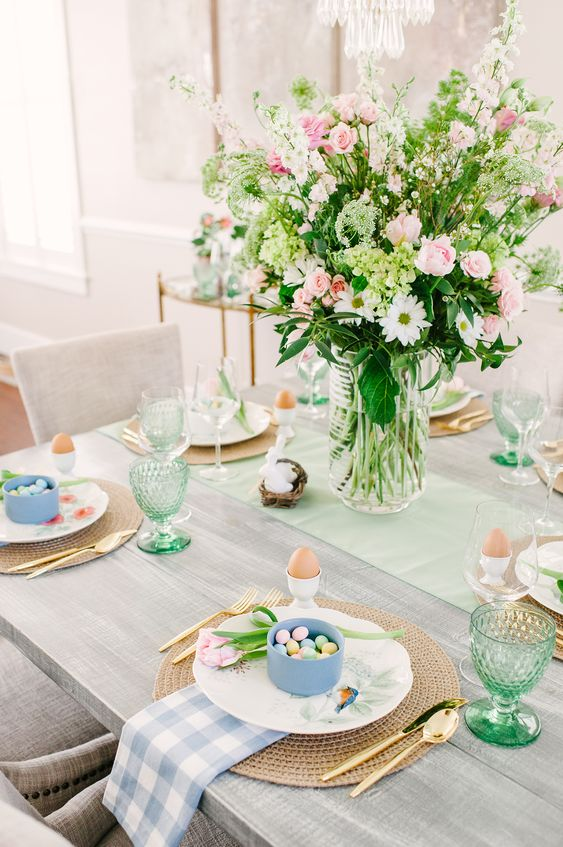 a fresh and lovely spring centerpiece with white, green and pink blooms and greenery is a beautiful option